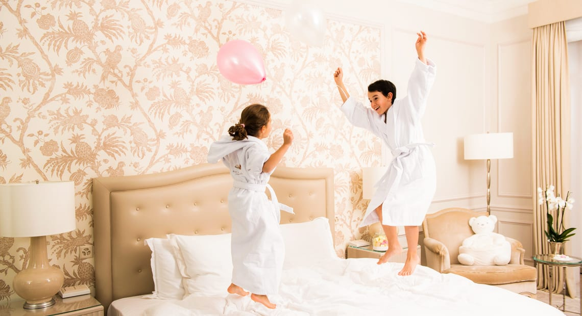 Two children jumping on a bed at hotel Beau Rivage