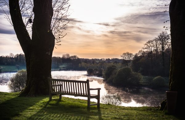 A bench in front of a lake at Le Domaine des Étangs *****