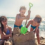 Kids building a sand castle by the beach near Grand Hôtel Thalasso & Spa