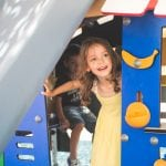 Little girl plays on the playground of the kids club at Ikos Olivia