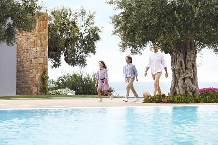 A family walking along the pool at Ikos Olivia
