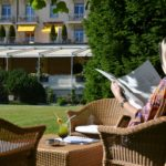 A woman reading a newspaper in the Gstaad Palace garden