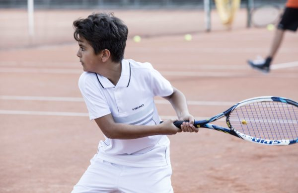 A boy playing tennis at Gstaad Palace
