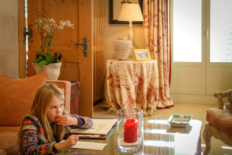 A little girl writing a letter in the room at Gstaad Palace