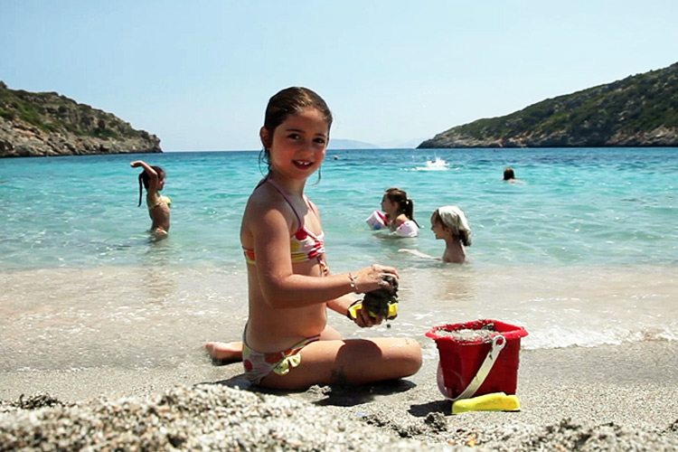 Little girl playing on the sand Daios Cove