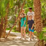 Family walking in the garden of Forte Village Resort