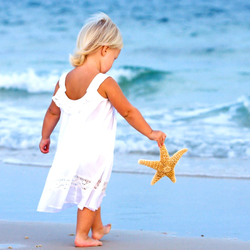 Baby girl playing on the beach with a starfish