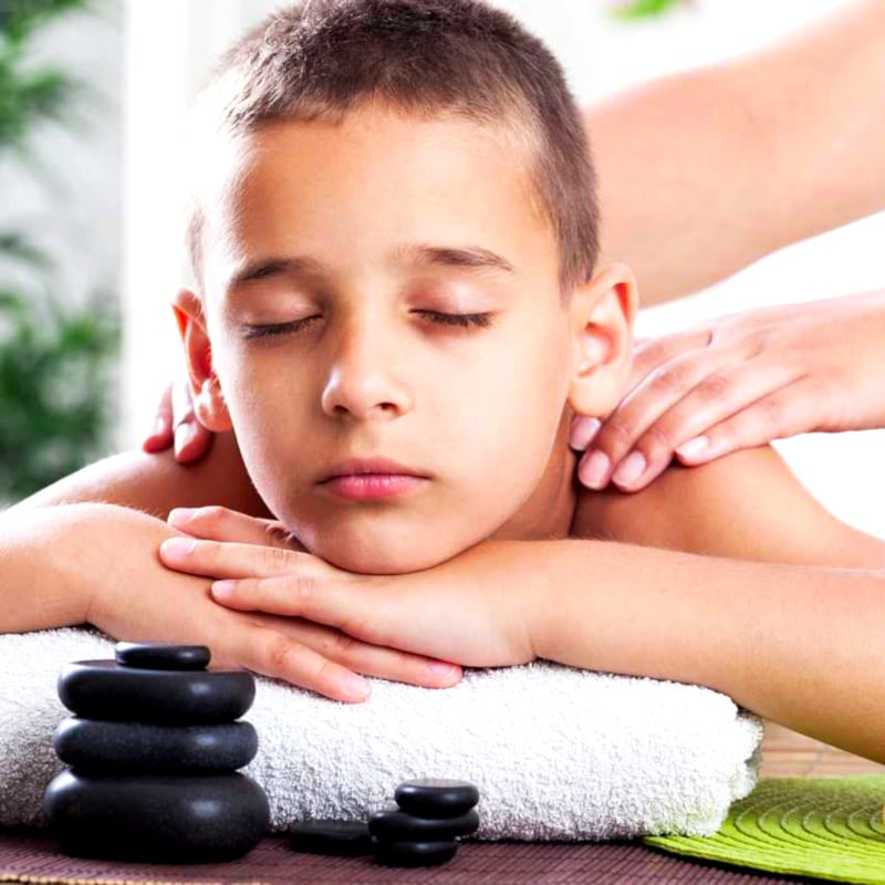 Little boy enjoying a massage in a spa