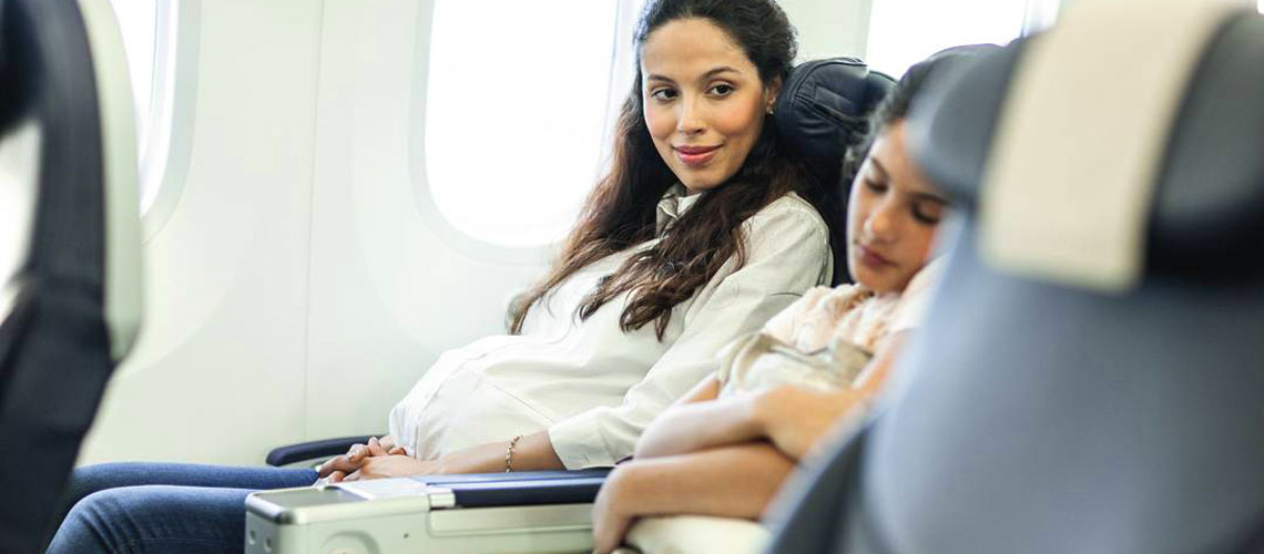 A future mum looks at her sleeping kid on an airplane