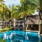 Outdoor pool surrounded by palm trees at Constance Belle Mare Plage