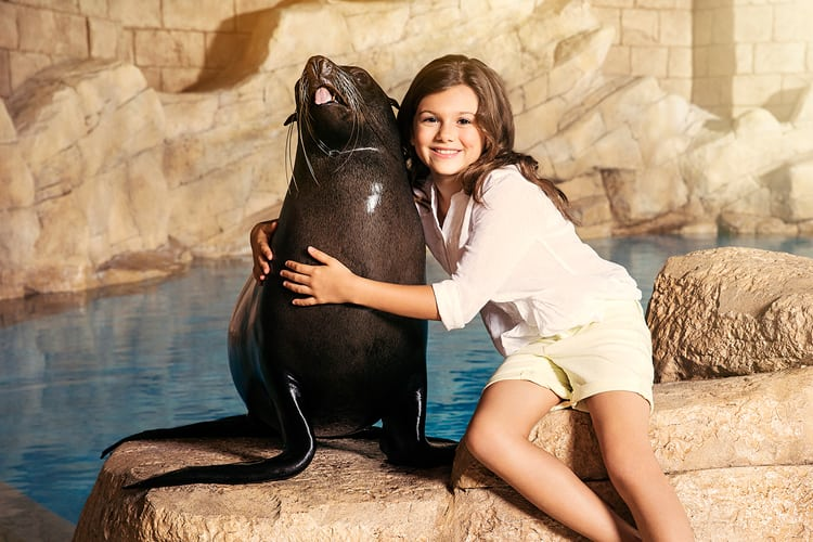 A little girl hugging a sea lion at Atlantis The Palm Dubaï