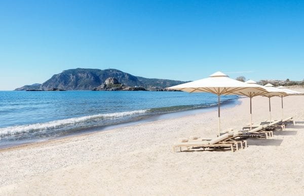 Ikos Aria beach with deckchairs and umbrellas