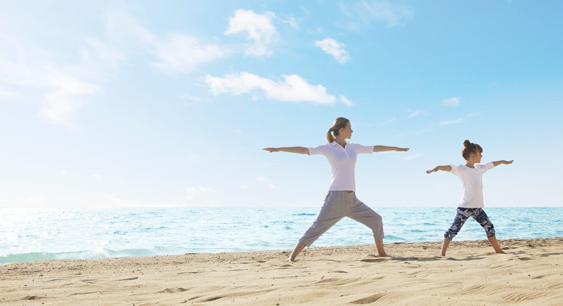 family yoga on the beach at ikos aria