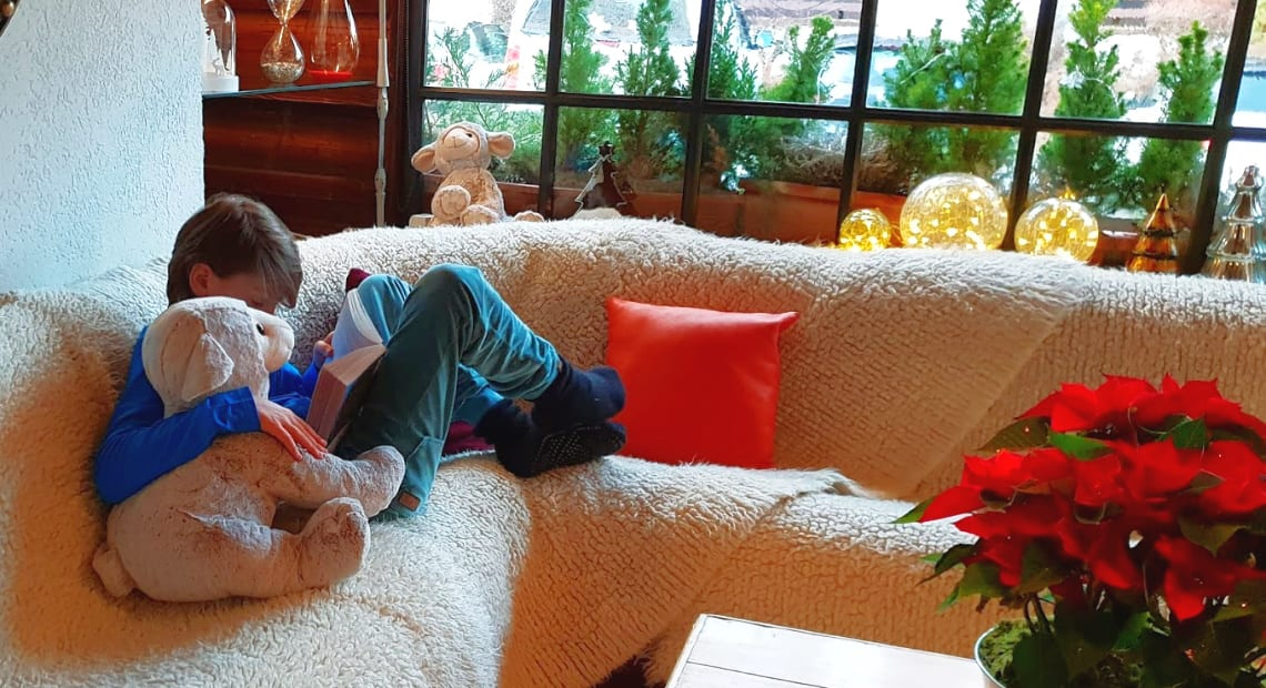 A kid reads a book at La Bergerie luxury hotel in Morzine