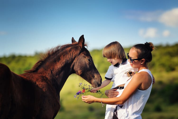Child petting a horse with his mom Dunton Hot Springs