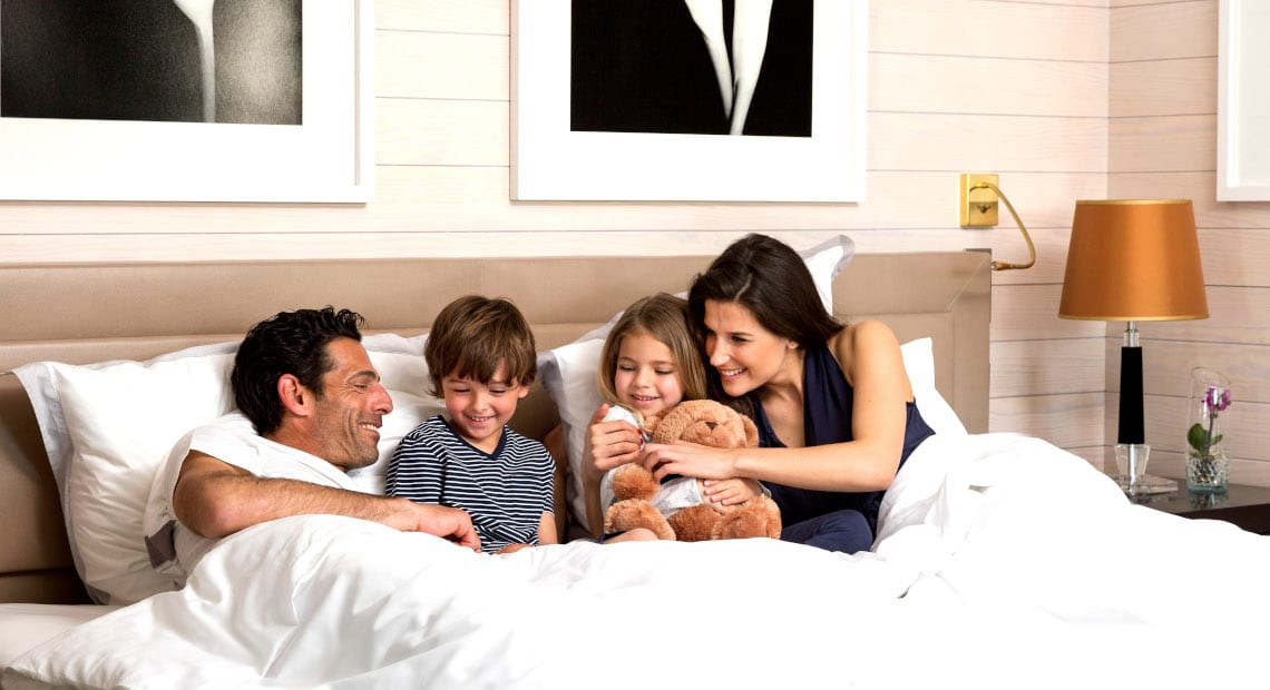 A family enjoy the comfort of the family room at the Hotel Barrière Le Majestic Cannes