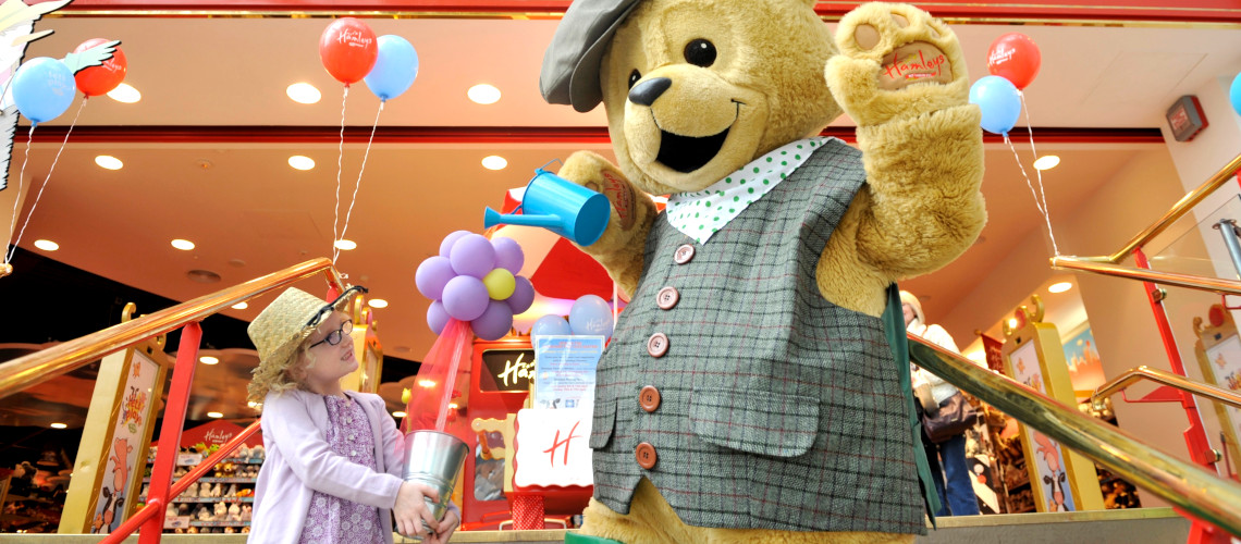 A babygirl plays with a giant teddy bear in front of the Hamleys store in London