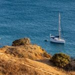 Woman walking on a hill close to sea with sailboat at Cascade Wellness Resort