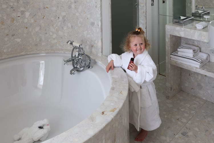 A baby girl in her bathrobe smiles in the bathroom at the Hotel De Sers in Paris