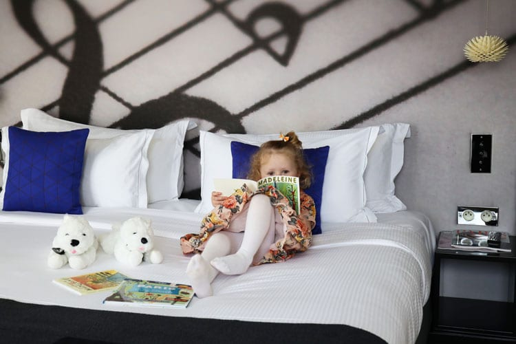 A baby girl reads a book in the parents' bed at Hotel De Sers in Paris