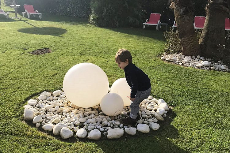 A boy playing at Les Flamants Roses hotel garden