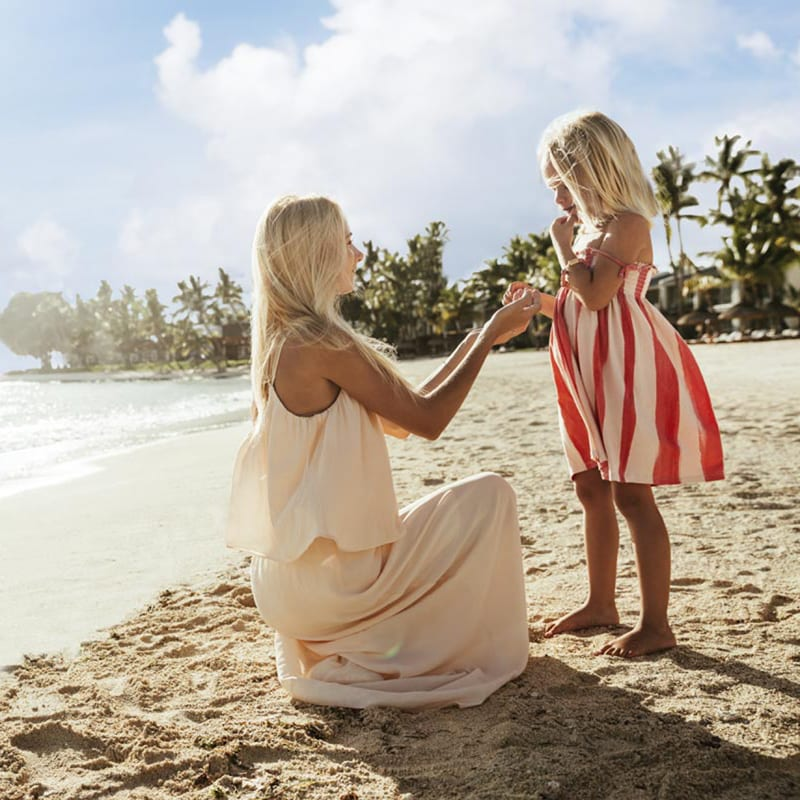 A mum and her daughter play together on the beach