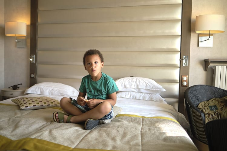 Kid sitting on the bed of one of the Grand Hotel des Thermes bedrooms in Saint-Malo