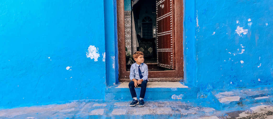A little boy sitting in one of the Chefchaouen street in Morocco