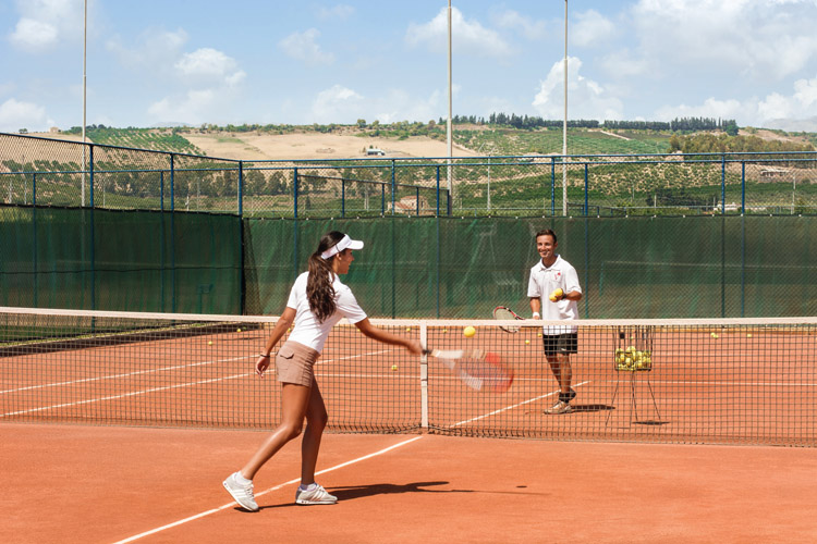 A family plays tennis on the tennis court at Verdura Resort in Sicily