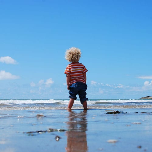 A child walking on the beach and catching the waves