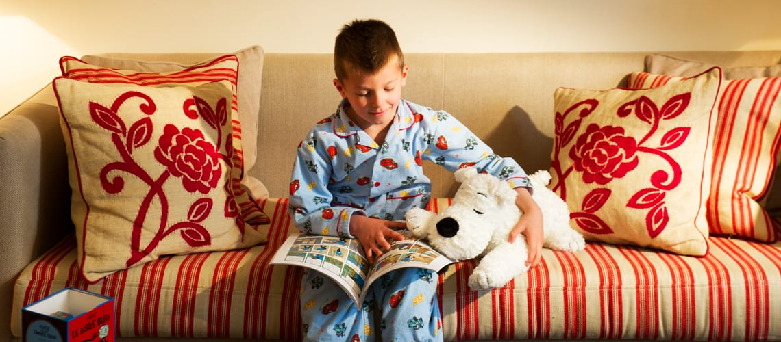A young boy reads Tintin aventures comics on his bed at Amigo hotel in Brussels