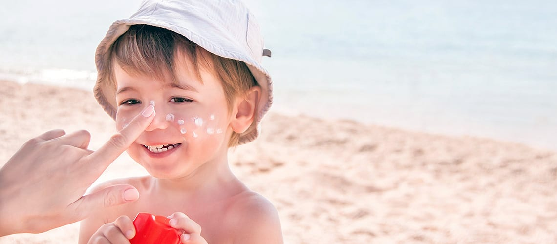 A child with sunscreen on his nose