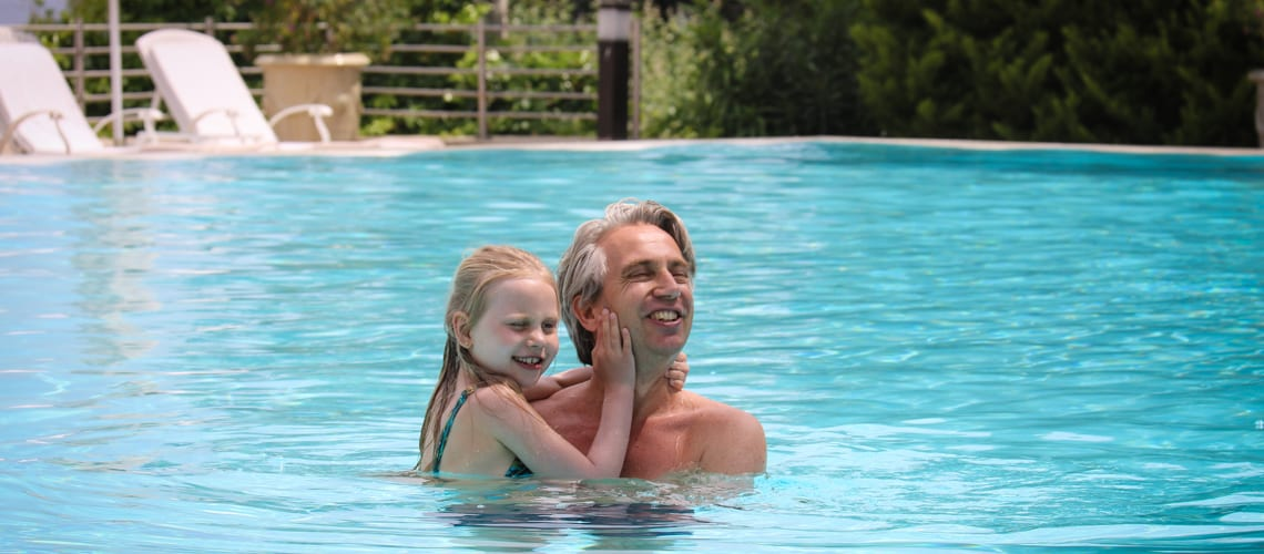 A father and his babygirl play in the pool together