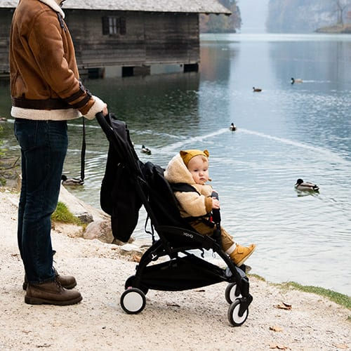 A dad holding a stroller with his baby