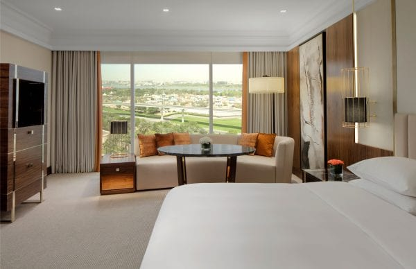 Grand Hyatt Dubai suite with double bed, sitting area and view on the skyline
