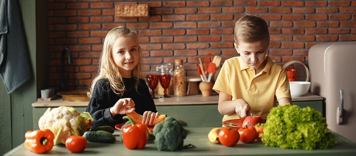children cooking and cutting vegetables