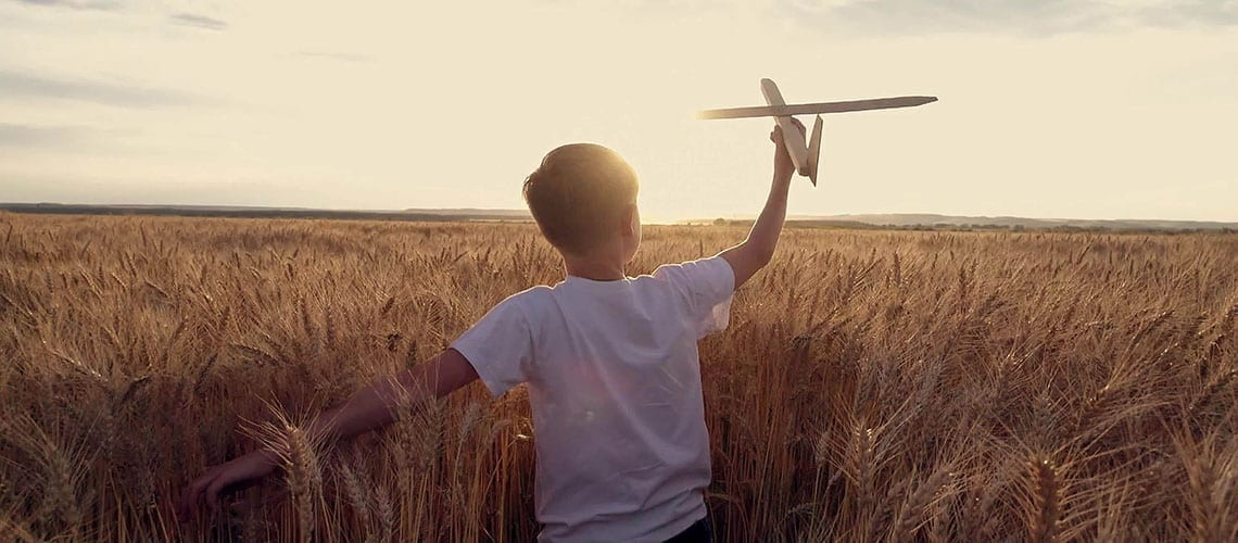 kid playing with a wooden plane