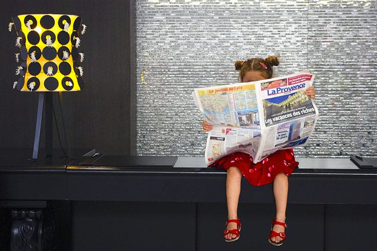 A child reading the newspaper at Intercontinental Marseille