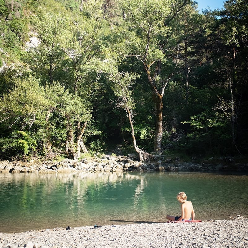 A boy by the lake in France at the Gorges du Verdon