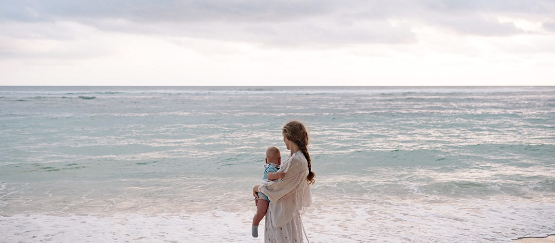 A mom and her baby by the beach
