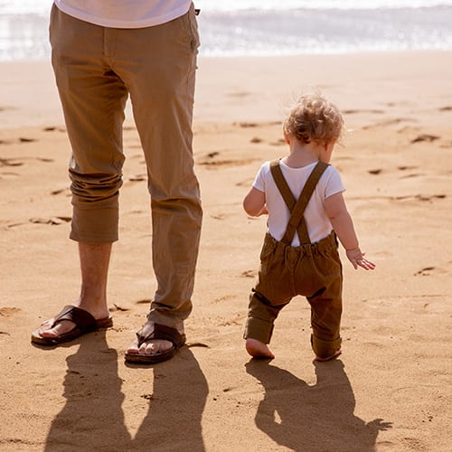A dad and his baby at the beach