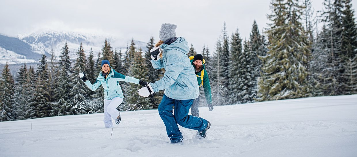 Family with small daughter having fun outdoors in winter nature